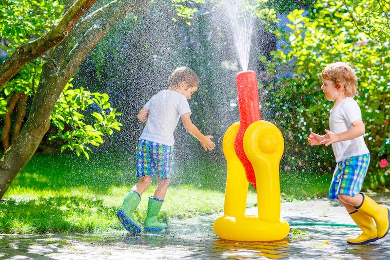Two boys playing in the sprinkler to keep cool, because their Springfield, Oregon, air conditioner is blowing out hot air.