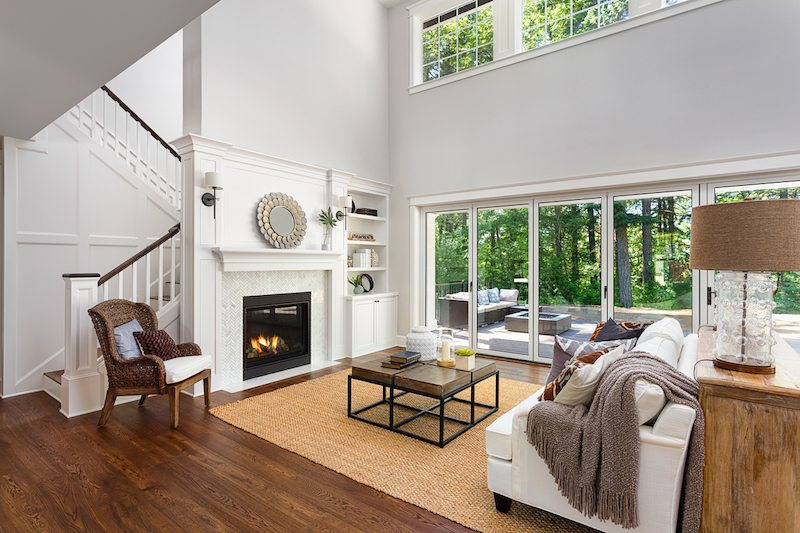 Beautiful living room interior with hardwood floors and fireplace in new luxury home with sliding glass doors and vaulted ceiling where new furnace filters are needed.