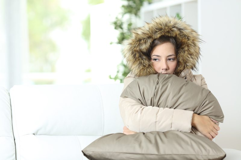 Angry woman warmly clothed in a cold home sitting on a couch.